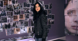 Jessica Jones in a room full of photos of herself.